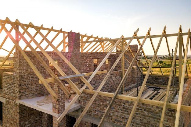 建設中の木造屋根構造の未完成のれんが造りの家。 Premium写真