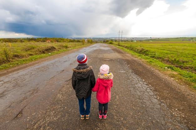 Двое маленьких детей мальчик и девочка гуляют по дороге Premium Фотографии