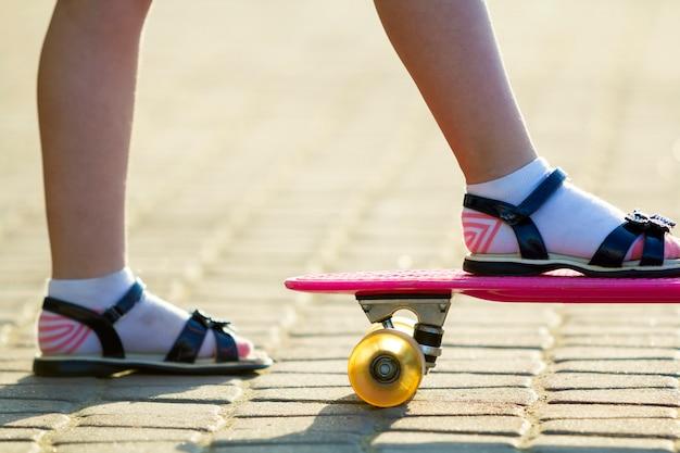 Детские ножки на пластиковом розовом скейтборде Premium Фотографии