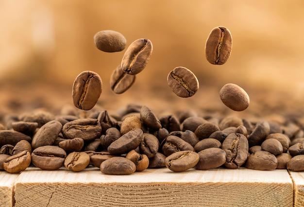 Летающие свежие кофейные зерна в качестве фона с копией пространства Premium Фотографии