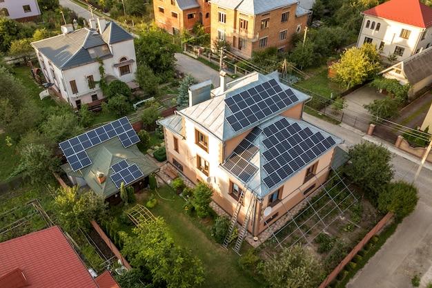 屋根の上の青い光沢のある太陽光写真太陽光発電パネルシステムと新しいモダンな住宅コテージの空中の平面図。再生可能な生態学的なグリーンエネルギー生産の概念。 Premium写真