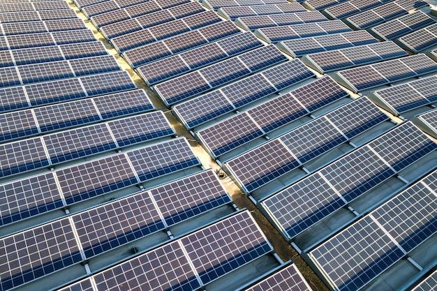産業用建物の屋根に取り付けられた多くの太陽光発電太陽電池パネルの航空写真。 Premium写真