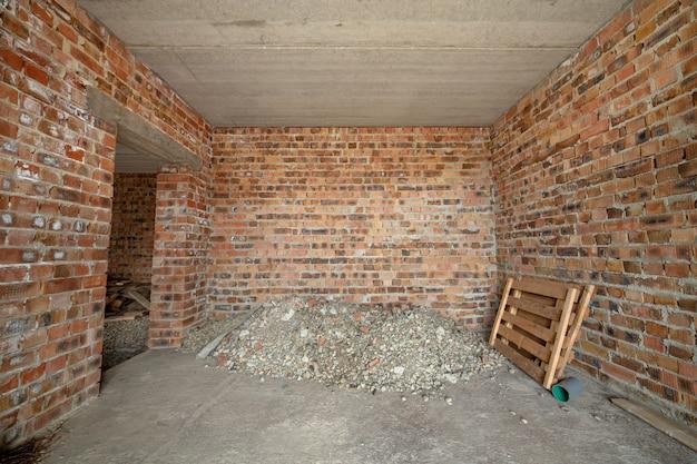 未完成のれんが造りの家の内部。コンクリートの床と裸壁で、左官工事の準備ができています。不動産開発 Premium写真