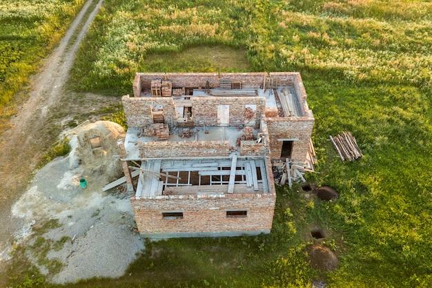将来の家、レンガの地下階、レンガの山の建設現場の空撮。 Premium写真