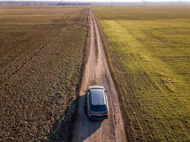 日当たりの良い青空コピースペース背景に緑のフィールドを介してまっすぐな地上道路で運転する車の空撮。ドローン写真。 Premium写真