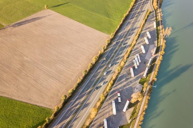 高速移動する交通のある高速道路の州間道路と駐車されたトラックの駐車場の空撮を上から見下ろしてください。 Premium写真