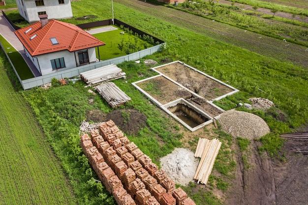 将来のれんが造りの家、コンクリート基礎床、建設用の黄色の粘土レンガのスタックの建設現場の空撮。 Premium写真