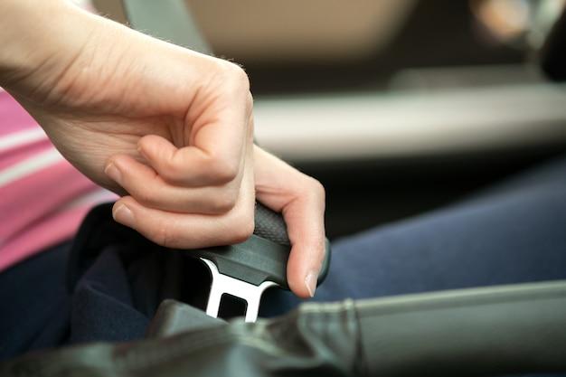 安全のために車の中に座って道路を運転する前にシートベルトを締めている女性の手のクローズアップ Premium写真