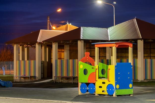 Красивая новая современная игровая площадка в детском саду с мягким резиновым полом и яркой новой разноцветной большой игрушечной машинкой Premium Фотографии