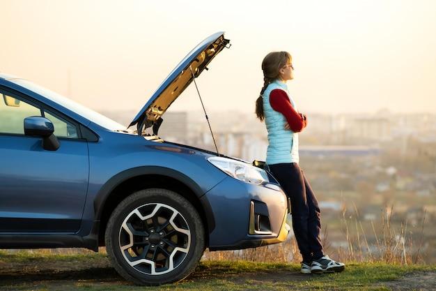 フードがポップアップした故障した車の近くに立っている若い女性は、彼女の車に問題があります。誤動作オートの横で助けを待っている女性ドライバー。 Premium写真