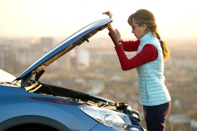 壊れた車のボンネットを開く若い女性が彼女の車に問題があります。フードがポップアップした自動車の近くの女性ドライバー。 Premium写真