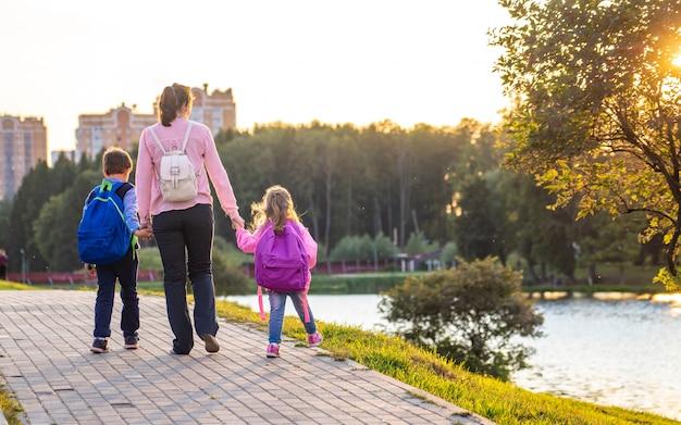 Женщина и двое детей со спины. Premium Фотографии