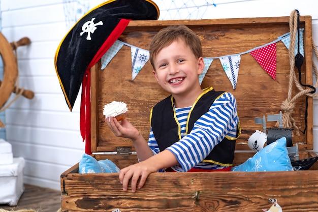 Мальчик в форме пиратов у руля. Premium Фотографии