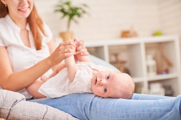 体操の赤ちゃん。その開発のための赤ちゃんと一緒に運動をしている女性。小さな新生児をマッサージします。 Premium写真