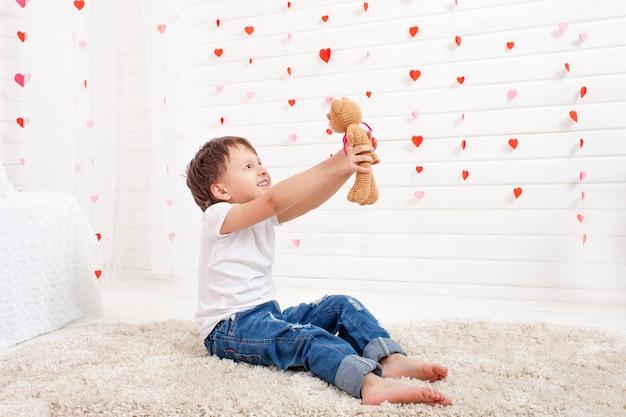 Маленький счастливый мальчик играет с игрушечным мишкой амигуруми Premium Фотографии