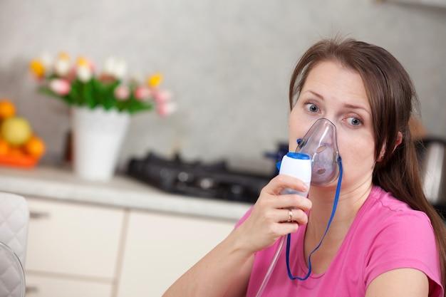 Молодая женщина делает ингаляции с помощью небулайзера в домашних условиях Premium Фотографии