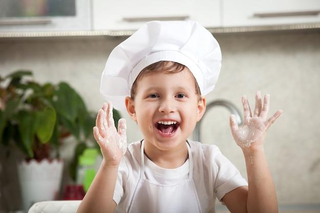 Забавный малыш с мукой, счастливый эмоциональный мальчик счастливо улыбается Premium Фотографии