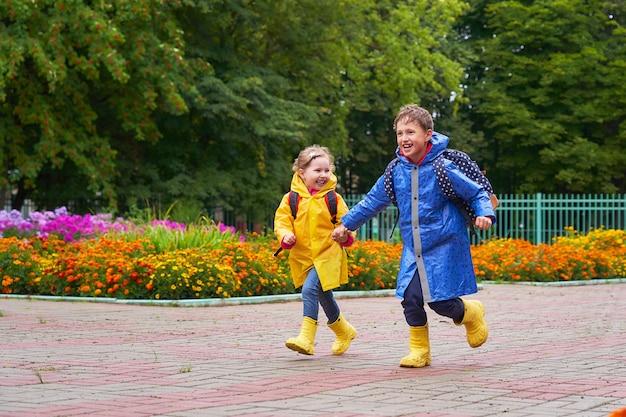幸せな子供たちは、急いで笑い、バックパックの後ろにブリーフケースを着てレインコートを着て学校に走ります。 Premium写真