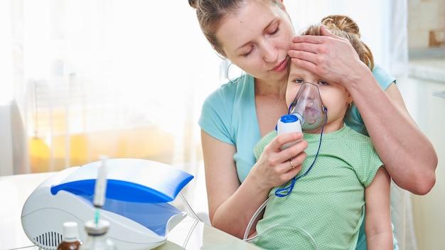 女性はマスクを通して子供に呼吸するのを助けます Premium写真