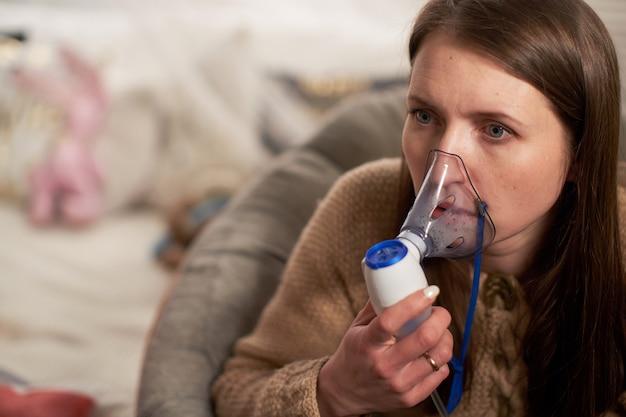 女性は自宅で吸入ネブライザーを作ります。マスクのネブライザーを吸入し、肺の病気の患者に薬を噴霧します。 Premium写真