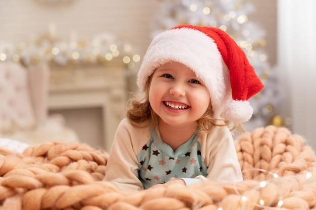 メリノベージュのデザイナーブランケット!サンタの帽子で笑っている子。背景の女の子の後ろには窓際のクリスマスツリーがあります Premium写真