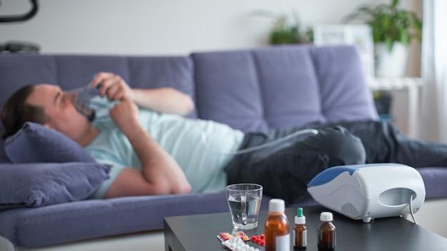 彼がぼやけているソファに横たわっている病人 Premium写真