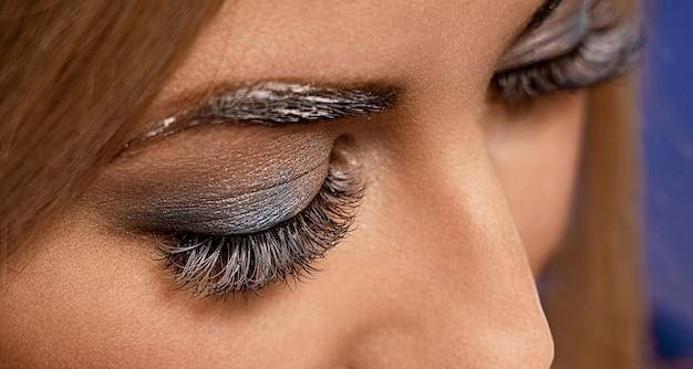 Красивый макросъемка женского глаза с очень длинными ресницами и черным макияжем. Premium Фотографии