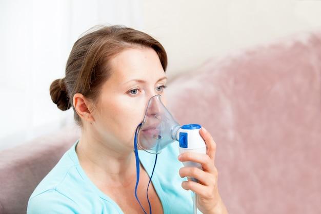 自宅でネブライザーで吸入を行う若い女性 Premium写真