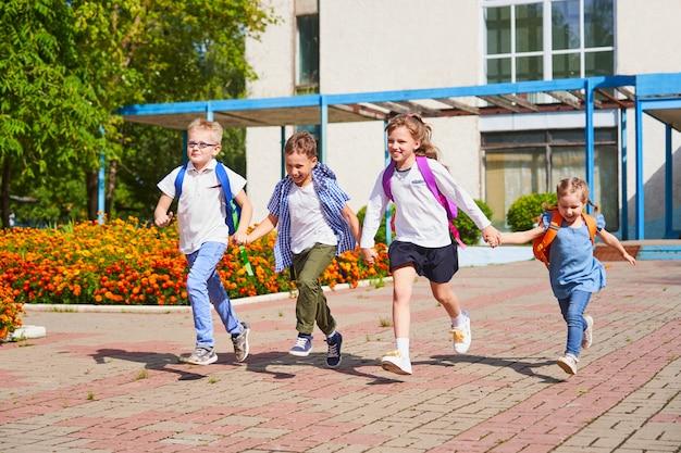 Группа школьников выбегает из школы Premium Фотографии