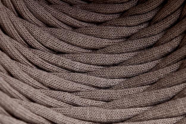 Моток серого трикотажной пряжи крупным планом. макросъемка фоновой текстуры узор переплетения волокон текстильной ткани. полоски ткани переплетаются на катушке. Premium Фотографии