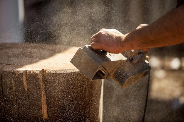 Плотник работает с электрическим рубанком на деревянном пне на открытом воздухе Premium Фотографии