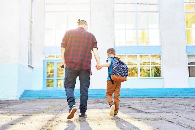 Обратно в школу. счастливый отец и сын идут в начальную школу Premium Фотографии