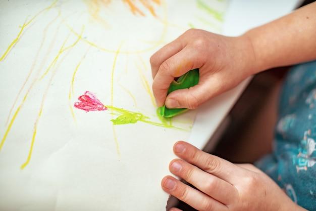 子供は自分の手で作ったワックスクレヨンで紙に花を描きます Premium写真