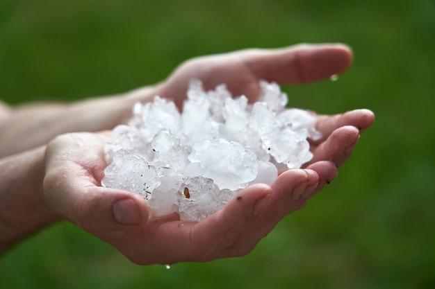 Большие кусочки льда окутывают вашу ладонь. человек, держащий горсть крупных град последствия природных аномалий. Premium Фотографии
