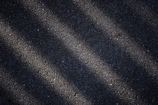 フェンスの暗い影のアスファルト道路。抽象的なストライプは明るい色と暗い色です。 Premium写真