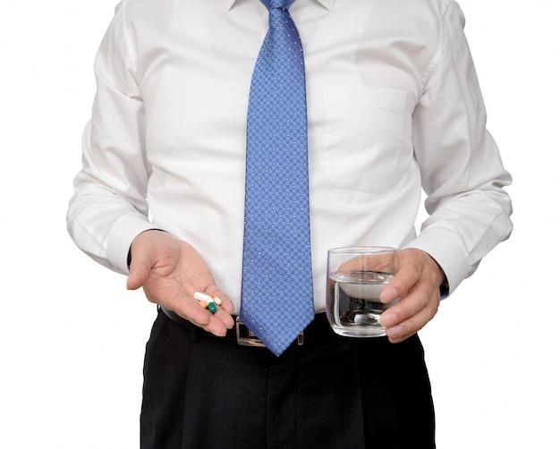 ピルと水カップを手に保持している実業家。 Premium写真