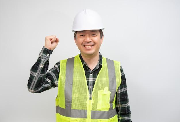 Азиатский мужчина средних лет в светло-зеленом рабочем жилете и белой шляпе безопасности. Premium Фотографии