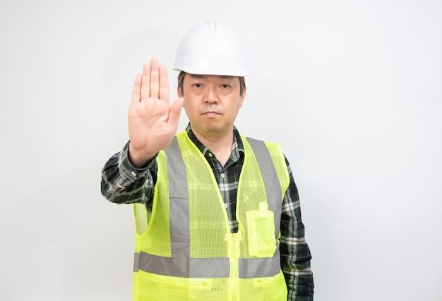 Азиатский работник средних лет, который поднимает руку и выражает свое неодобрение. Premium Фотографии