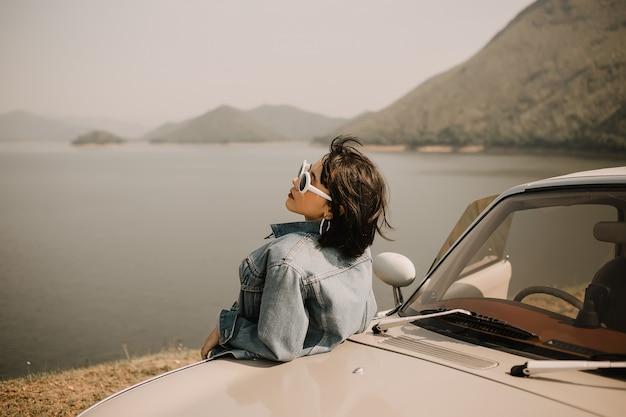 湖でリラックスした若い女性。彼女はクラシックカーで湖に行きます。彼女はサングラスをかけています。 Premium写真