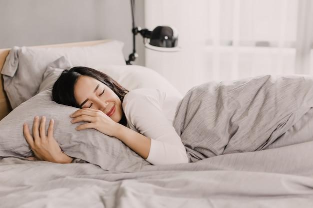 幸せなアジアの女性はベッドの上の優しい枕で休んでいます Premium写真