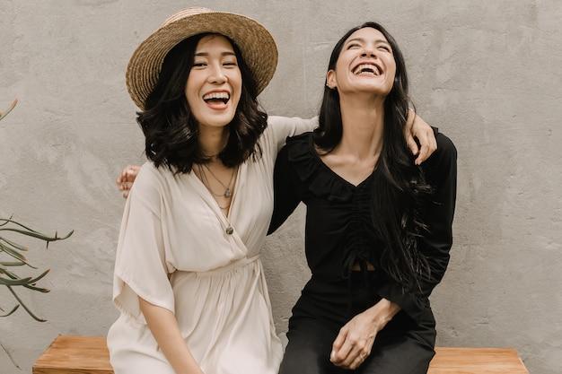 Две азиатские женщины обнимаются вместе, пока они смеются и улыбаются Premium Фотографии