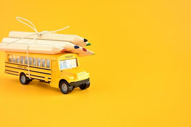 屋根の上に鉛筆でおもちゃのスクールバス。 Premium写真