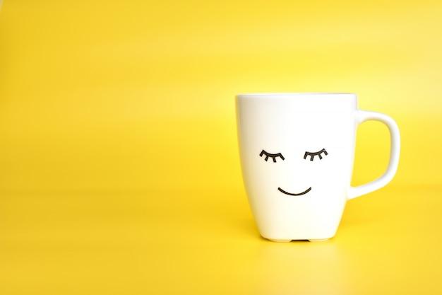 ホワイトティーまたはコーヒーカップ、かわいい目を閉じて顔、おはよう Premium写真