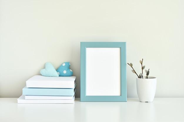 水色のインテリア、空白のフォトフレームモックアップ、書籍、白と青の装飾。 Premium写真