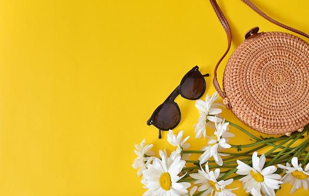Летняя мода, женские аксессуары, круглая сумка из ротанга, солнцезащитные очки, цветы на желтом. Premium Фотографии