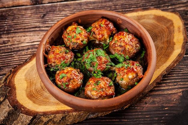 グルジア料理のコンセプト。焼きキノコのシャンピニオンと肉とコリアンダー。赤い粘土で作られたプレートのレストランで料理を提供します。木製の背景に。コピースペース Premium写真