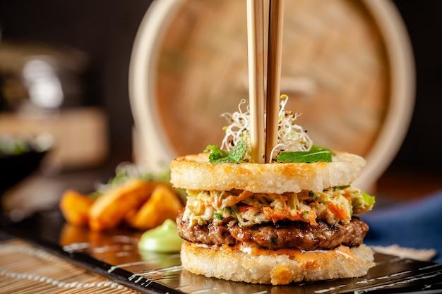 Концепция паназиатской кухни. японский суши бургер из рисового хлеба, пирожков с курицей и свининой, листьями салата и соусом васаби. сервировка блюд с картофелем фри. копировать пространство Premium Фотографии