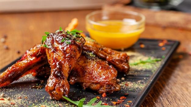 Концепция индийской кухни. запеченные куриные крылышки и ножки в медово-горчичном соусе. сервировка блюд в ресторане на черной тарелке. индийские специи на деревянном столе. изображение на заднем плане. Premium Фотографии