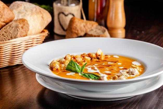 イタリア料理のコンセプト。オレンジ風味のチキンパンプキンクリームスープ、チキンピース、パンクルトン、クリーム。テーブルの上の赤ワインの文字列。レストランで料理を提供 Premium写真