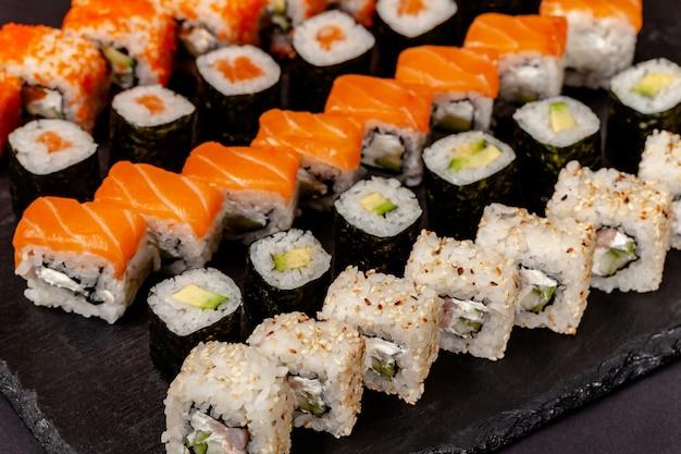 寿司とロールから設定された石の黒板にあります。 Premium写真